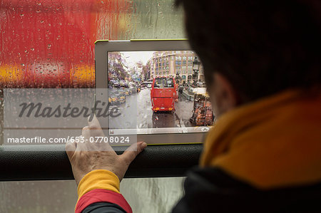 Rear view of woman photographing bus with digital tablet Stock Photo - Premium Royalty-Free, Image code: 653-07708024