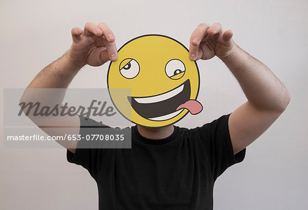 Man holding a funny emoticon face in front of his face Stock Photo - Premium Royalty-Free, Image code: 653-07708035