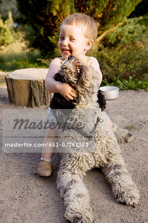 Baby girl playing with Portuguese Water Dog Stock Photo - Premium Royalty-Free, Image code: 653-07761353