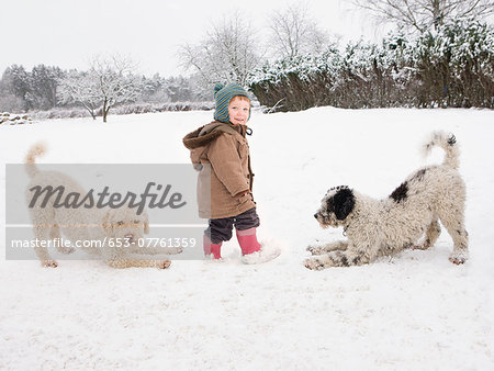 Baby girl with Portuguese Water Dogs in snow Stock Photo - Premium Royalty-Free, Image code: 653-07761359