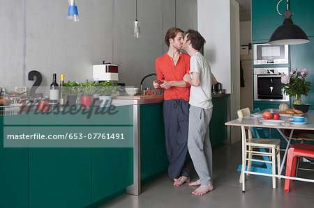 Full length of romantic gay couple kissing in kitchen Stock Photo - Premium Royalty-Free, Image code: 653-07761491