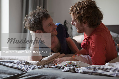 Affectionate gay couple looking at each while relaxing in bedroom Stock Photo - Premium Royalty-Free, Image code: 653-07761496