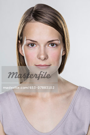 Close-up portrait of beautiful young woman against white background Stock Photo - Premium Royalty-Free, Image code: 653-07883102