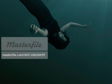 A woman with closed eyes and blank expression, sinking underwater Stock Photo - Premium Royalty-Free, Image code: 653-08126097