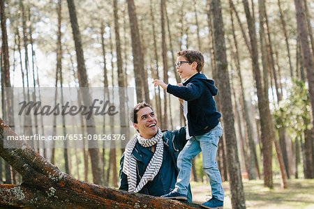 Happy father assisting son in climbing tree at forest Stock Photo - Premium Royalty-Free, Image code: 653-08126376