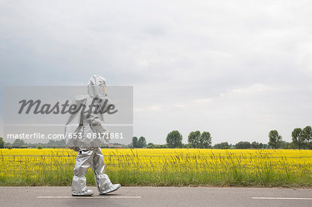 A person in a radiation protective suit walking alongside an oilseed rape field Stock Photo - Premium Royalty-Free, Image code: 653-08171881