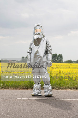 A person in a radiation protective suit standing in front of an oilseed rape field Stock Photo - Premium Royalty-Free, Image code: 653-08171882