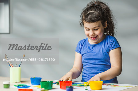 Smiling girl finger painting at home Stock Photo - Premium Royalty-Free, Image code: 653-08171890