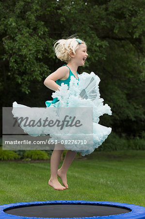 Happy girl bouncing on trampoline Stock Photo - Premium Royalty-Free, Image code: 653-08276710