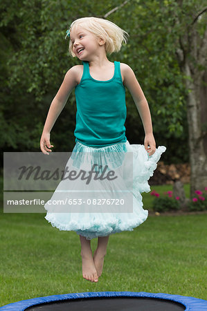 Happy girl jumping on trampoline Stock Photo - Premium Royalty-Free, Image code: 653-08276720