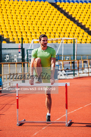 Full length of track and field athlete warming up on hurdle at sports track Stock Photo - Premium Royalty-Free, Image code: 653-08382250