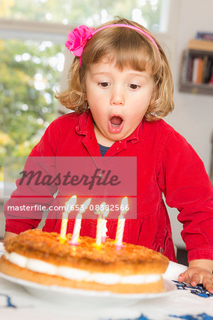 Cute girl blowing birthday candles at table Stock Photo - Premium Royalty-Free, Image code: 653-08382566