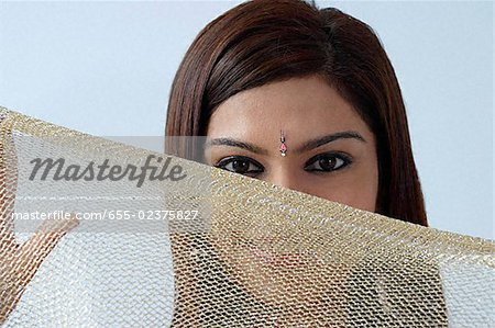 Young woman hiding behind veil Stock Photo - Premium Royalty-Free, Image code: 655-02375827