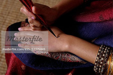 Indian woman painting hand with henna Stock Photo - Premium Royalty-Free, Image code: 655-02375845