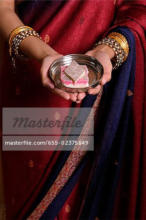 Indian woman offering sweets Stock Photo - Premium Royalty-Free, Image code: 655-02375849