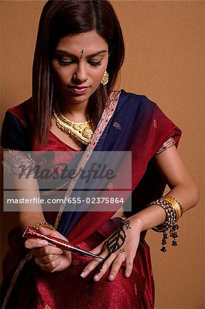 Indian woman painting hand with henna Stock Photo - Premium Royalty-Free, Image code: 655-02375864