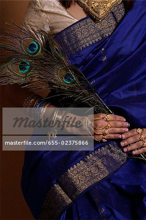 Torso of Indian woman holding peacock feathers Stock Photo - Premium Royalty-Free, Image code: 655-02375866