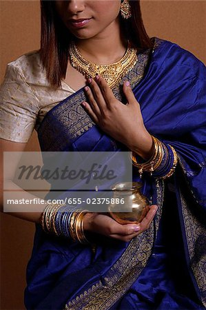 Indian woman wearing sari and holding offering Stock Photo - Premium Royalty-Free, Image code: 655-02375886