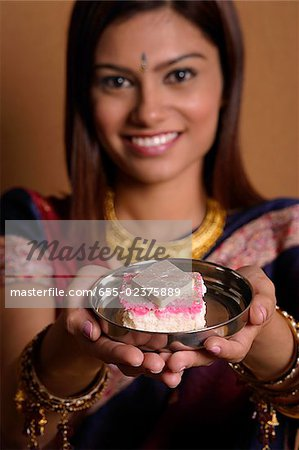Indian woman offering plate of sweets Stock Photo - Premium Royalty-Free, Image code: 655-02375889