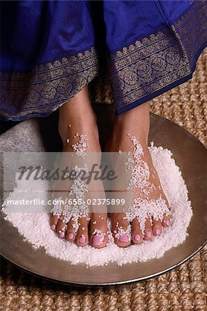 Indian woman with feet in salt scrub Stock Photo - Premium Royalty-Free, Image code: 655-02375899