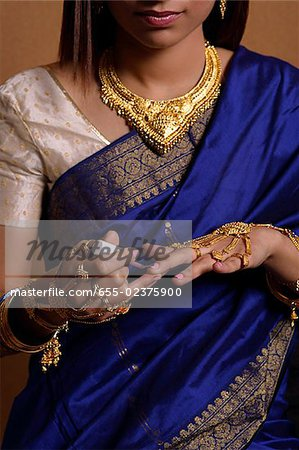 Indian woman painting her nails Stock Photo - Premium Royalty-Free, Image code: 655-02375900