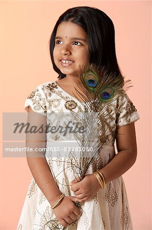 Little girl wearing traditional Indian clothing holding peacock feathers Stock Photo - Premium Royalty-Free, Image code: 655-02883050