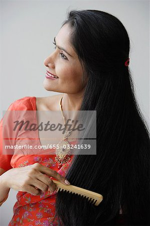 Indian woman smiling while combing hair Stock Photo - Premium Royalty-Free, Image code: 655-03241639