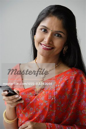 Indian woman wearing a sari and using a mobile phone Stock Photo - Premium Royalty-Free, Image code: 655-03241644