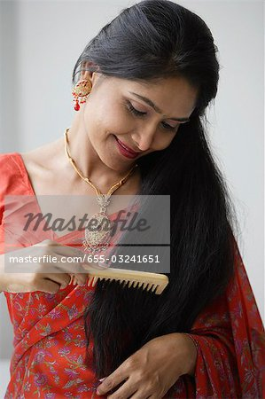 Indian woman wearing a sari and combing her hair Stock Photo - Premium Royalty-Free, Image code: 655-03241651
