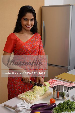 Indian woman wearing a sari while making dinner in the kitchen Stock Photo - Premium Royalty-Free, Image code: 655-03241687