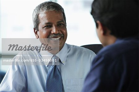 Two businessmen smiling at each other Stock Photo - Premium Royalty-Free, Image code: 655-03458001