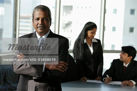 Mature Indian man standing in front of his colleages Stock Photo - Premium Royalty-Free, Image code: 655-03458039