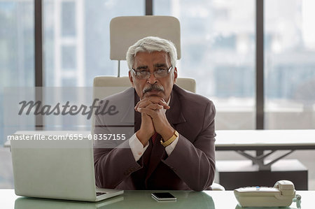 India, Portrait of senior businessman siting at desk with hands under chin Stock Photo - Premium Royalty-Free, Image code: 655-08357155