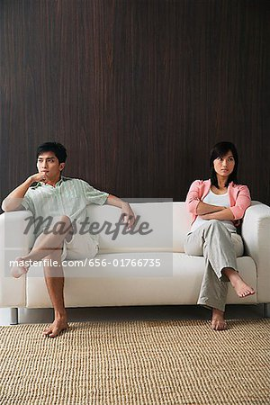Young couple sitting on opposite ends of the sofa Stock Photo - Premium Royalty-Free, Image code: 656-01766735