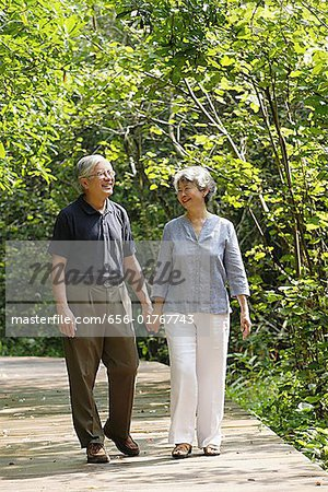 Mature couple walking through park, holding hands Stock Photo - Premium Royalty-Free, Image code: 656-01767743