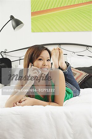 Girl in bedroom, lying on bed, using mobile phone, looking at camera Stock Photo - Premium Royalty-Free, Image code: 656-01771222