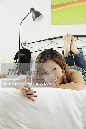 Girl in bedroom, lying on bed, holding mobile phone, looking at camera Stock Photo - Premium Royalty-Free, Image code: 656-01771223