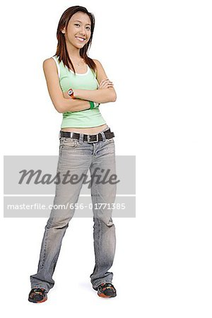 Young woman in tank top and jeans arms crossed, smiling at camera Stock Photo - Premium Royalty-Free, Image code: 656-01771385
