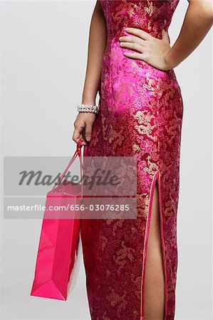 Cropped shot of woman wearing a pink cheongsam holding a shopping bag Stock Photo - Premium Royalty-Free, Image code: 656-03076285