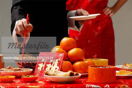 Crop shot of someone getting food during Chinese New Year party. Stock Photo - Premium Royalty-Free, Image code: 656-04926538