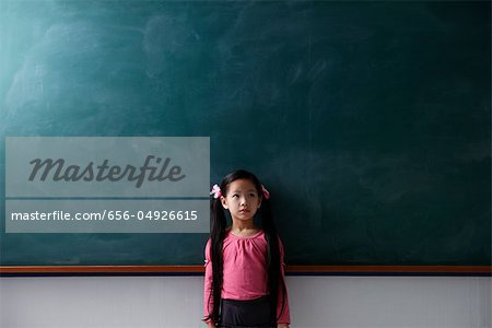 Young girl with pony tails standing in front of a chalk board Stock Photo - Premium Royalty-Free, Image code: 656-04926615