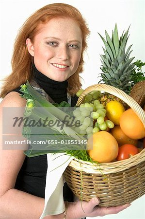 Young woman holding a basket of fruit and vegetables Stock Photo - Premium Royalty-Free, Image code: 659-01855145