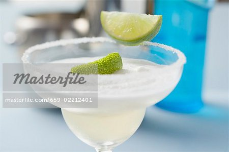 Margarita with lime wedges in a glass with a salted rim Stock Photo - Premium Royalty-Free, Image code: 659-02212401