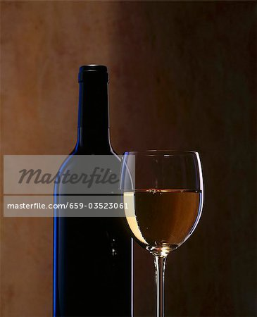 A glass of white wine and a wine bottle Stock Photo - Premium Royalty-Free, Image code: 659-03523061