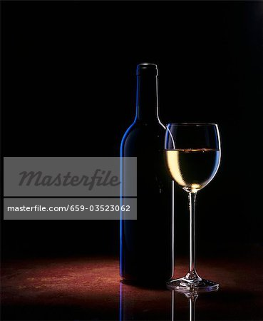A glass of white wine and a wine bottle Stock Photo - Premium Royalty-Free, Image code: 659-03523062