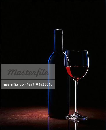 A glass of red wine and a wine bottle Stock Photo - Premium Royalty-Free, Image code: 659-03523063
