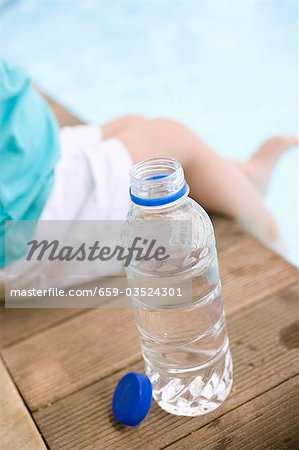 Child sitting beside bottle of water on edge of pool Stock Photo - Premium Royalty-Free, Image code: 659-03524301