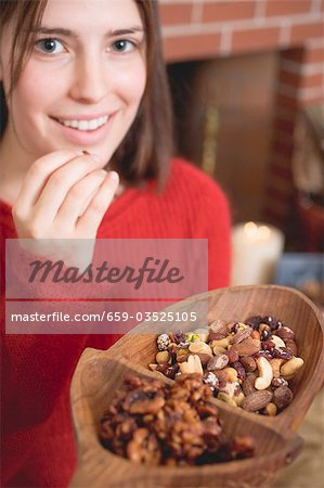 Young woman eating nuts in front of fireplace (Christmas) Stock Photo - Premium Royalty-Free, Image code: 659-03525105