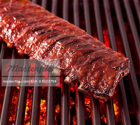 Whole Rack of Pork Ribs on Grill with Barbecue Sauce Stock Photo - Premium Royalty-Free, Image code: 659-03533799