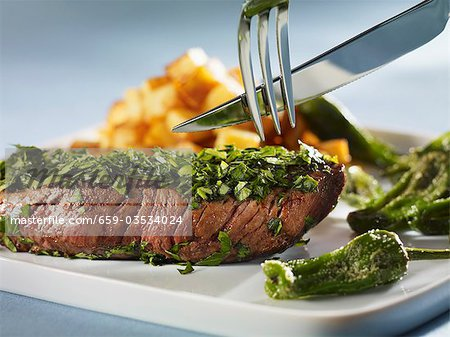 Steak coated in herbs with Pimientos de Padron Stock Photo - Premium Royalty-Free, Image code: 659-03534024